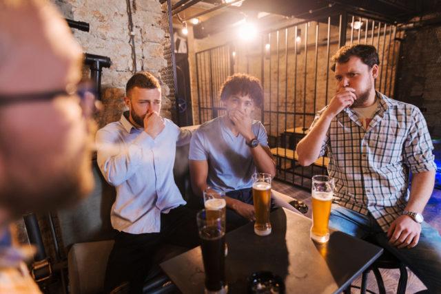 男性がタバコを吸っており、ほかの3人の男性が口を押さえている画像