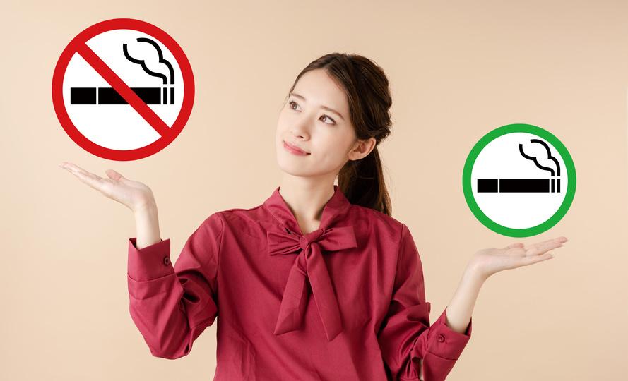 女性が喫煙可と禁煙のマークを天秤にかけている画像