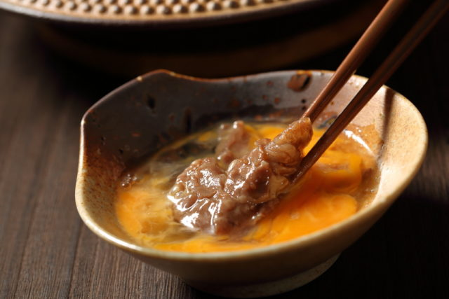 玉子にすき焼きのお肉をくぐらせている画像