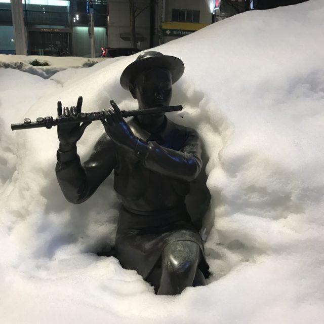 雪に埋もれた銅像の写真