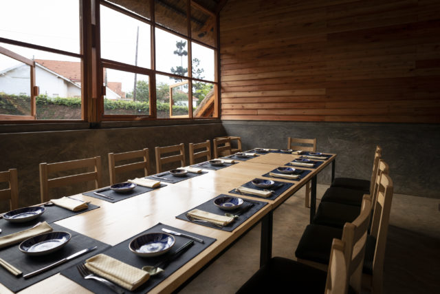 ウガンダにあるレストラン「YAMASEN」の内観。木のテーブルとイスがあり、大きな窓から外が見える