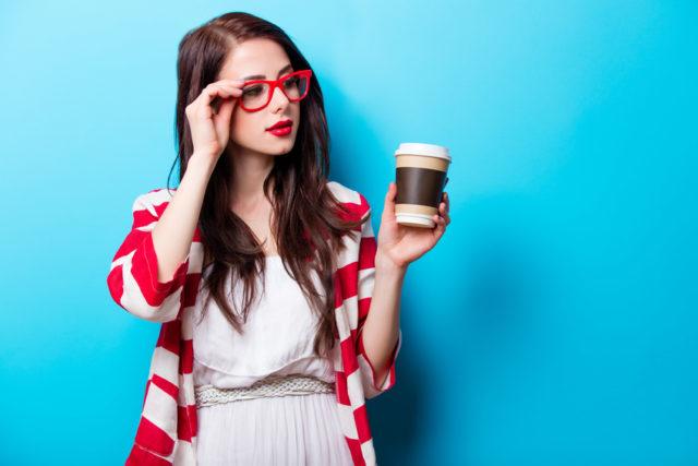 白いワンピース姿のメガネの女性がドリンクを片手に持って立ってる画像