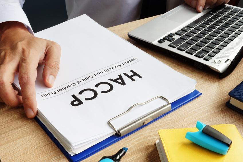 HACCAと書かれた紙とノートパソコンがデスクに置かれている画像