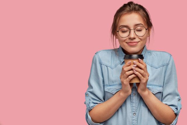 ジーンズシャツのメガネの女性がドリンクをもって微笑んでいる画像