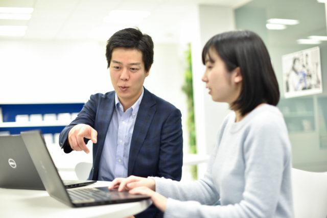 谷口さんが女性にノートパソコンで説明している様子