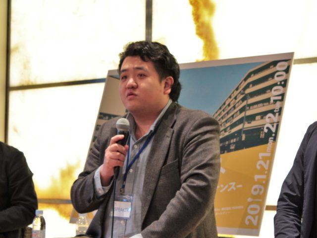 川越さんがマイクで話している写真