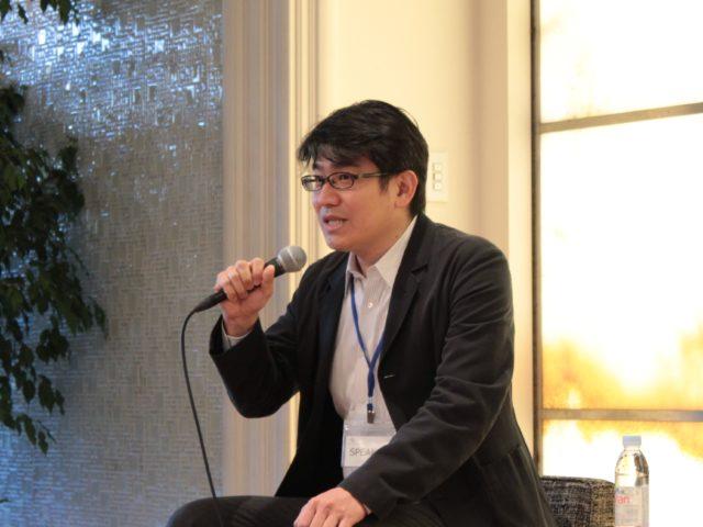 田中さんがマイクで話している写真