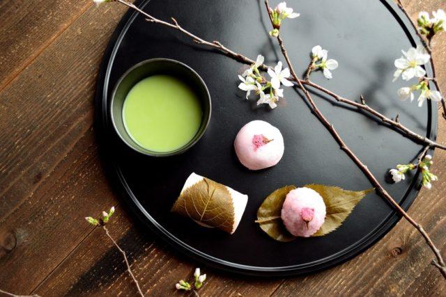 黒いおぼんの上に桜の和菓子と抹茶が置かれている画像