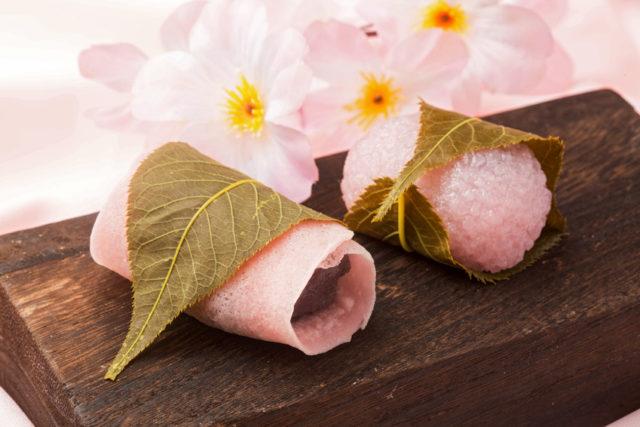 桜の花をバックに桜餅が置かれている画像
