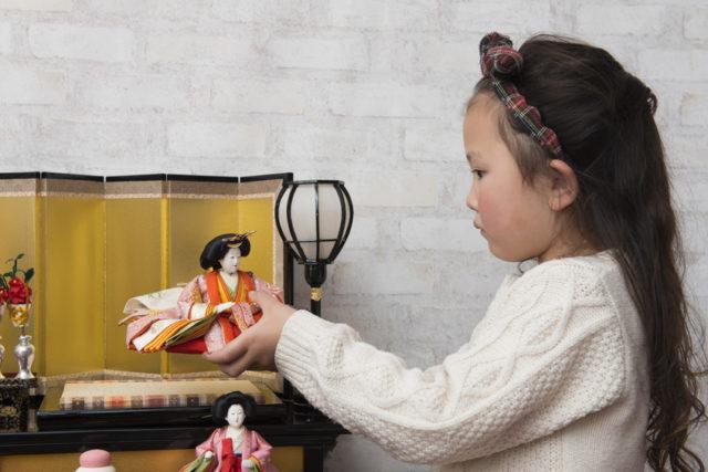 雛人形を飾る女の子の画像