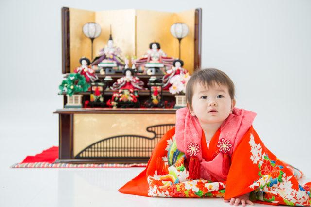 雛段の前に赤ちゃんが座っている画像