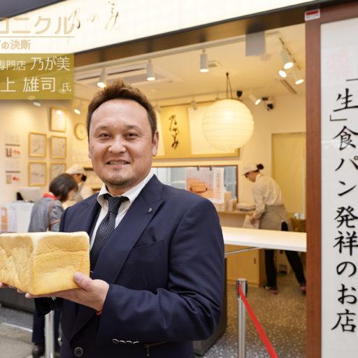 店頭で生食パンを手に阪上氏が立っている写真