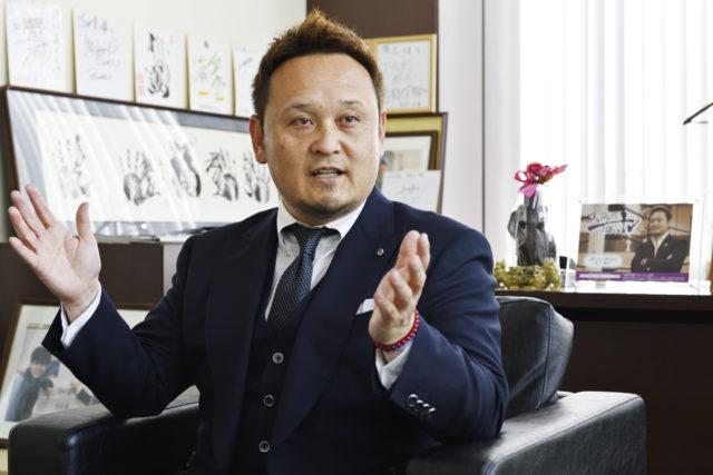 阪上氏がオフィスで両手を広げてインタビューにこたえている写真