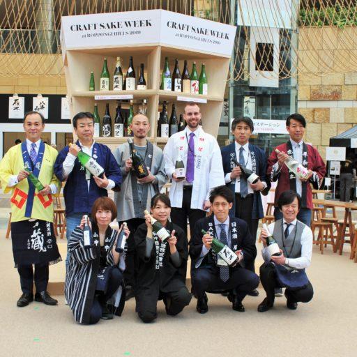 各酒蔵さんが手に酒瓶をもって集合写真を撮っている