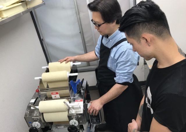 製麺機で麺をつくっている宮島さんと横で見ている生徒