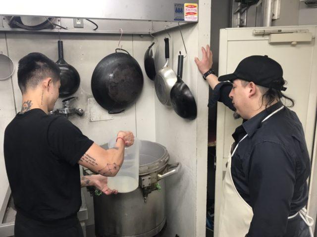 スープ用の水を寸胴鍋の中に注いでいるところ