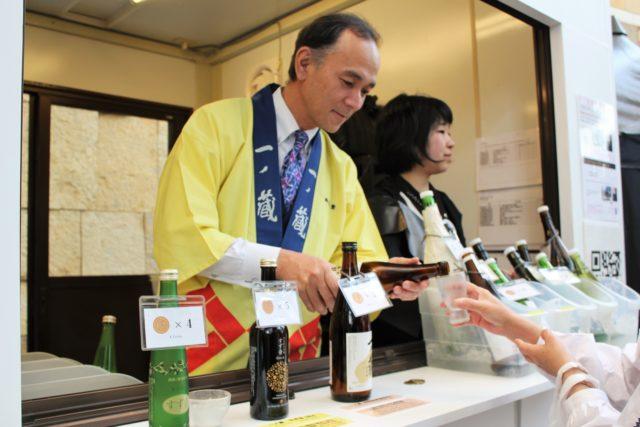 黄色い法被の宮城県の一ノ蔵の方がお酒を注いでいる写真