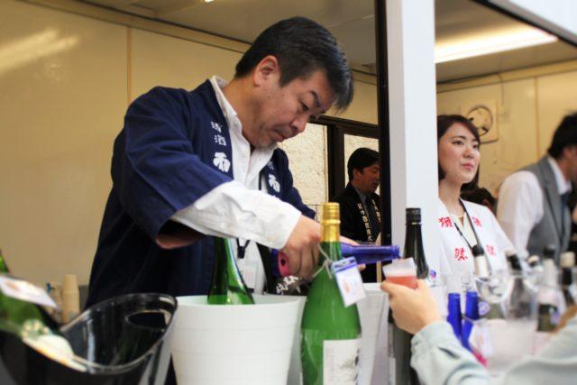 青い法被を着た広島県の相原酒造の方が日本酒を注いでいる写真