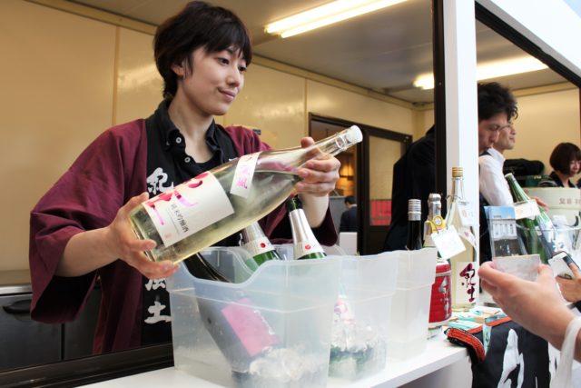 赤い法被の和歌山県の平和酒造の方が日本酒を注いでいる写真