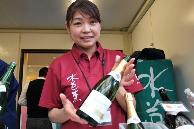 赤い「水芭蕉」と書かれたシャツを着た群馬県の永井酒造の女性が酒瓶を手に持っている写真