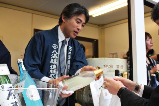 青い法被を着た新潟県八海醸造の男性が日本酒を注いでいる写真