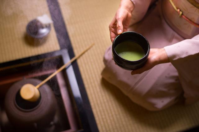 茶の間でお茶を手に持つ着物の女性の画像