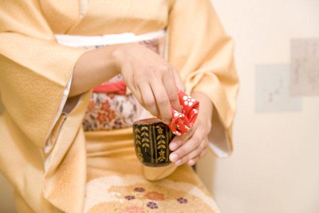 帛紗を手に持ち茶器をつかむ女性の手元の画像