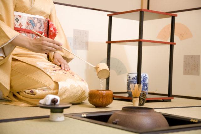 柄杓で湯をすくう女性の画像