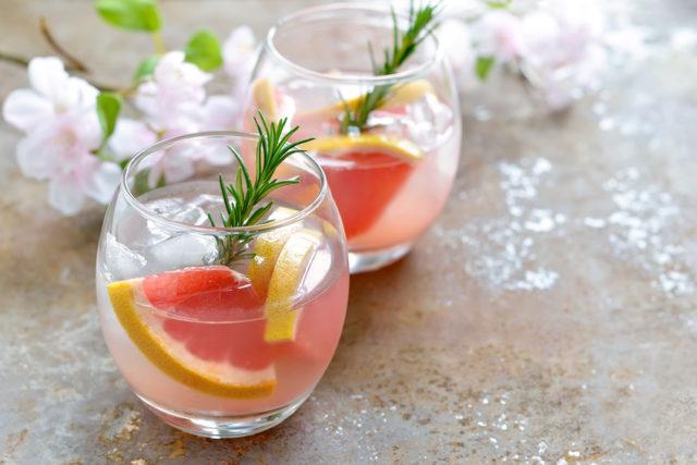 円いグラスにピンクグレープフルーツの入ったカクテルの画像