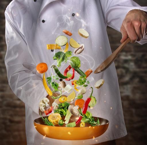 野菜を炒めるシェフの画像