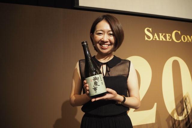 青木酒造の専務、青木知左さんが笑顔で酒瓶を持っている写真