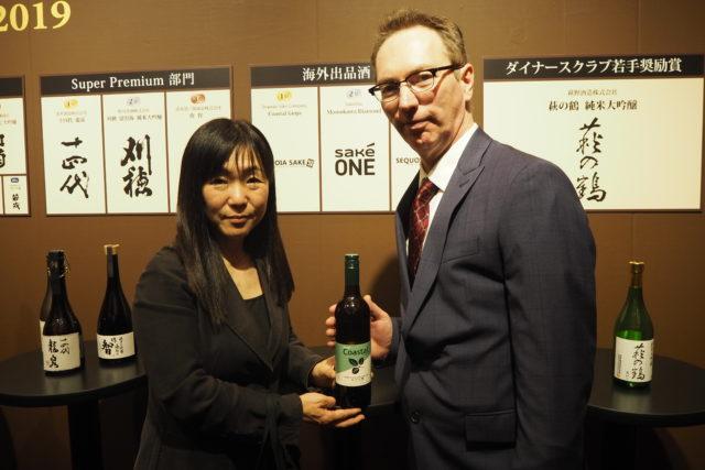 Sequoia Sake CompanyのJake Myrickさんと妻のNoriko Kameiさんが手に酒瓶を持って立っている写真