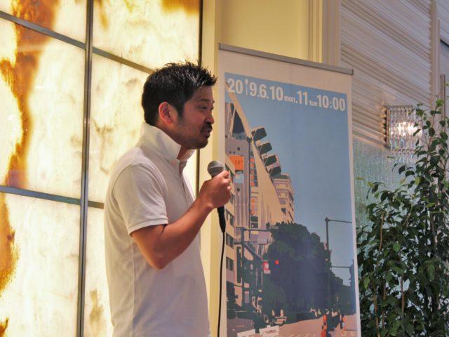主催者の松嶋さんがマイクを片手に話している写真