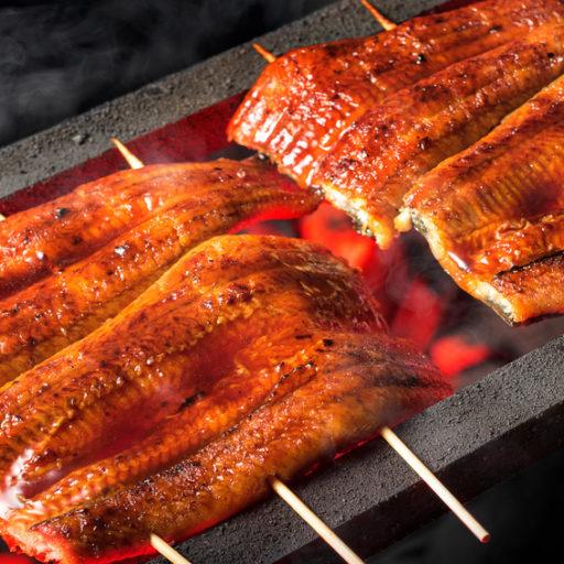 鰻の蒲焼が炭火で焼かれている画像