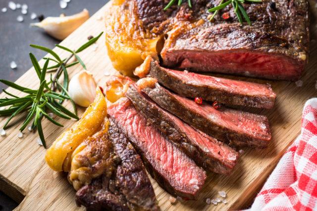 ウッドボードの上でグリルしたお肉をカットして並べているところ