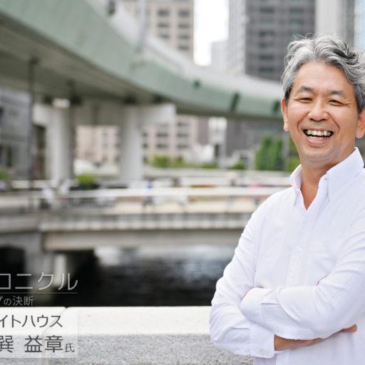 株式会社ライトハウスの巽益章氏が橋のたもとで笑顔で腕組みをして立っている写真
