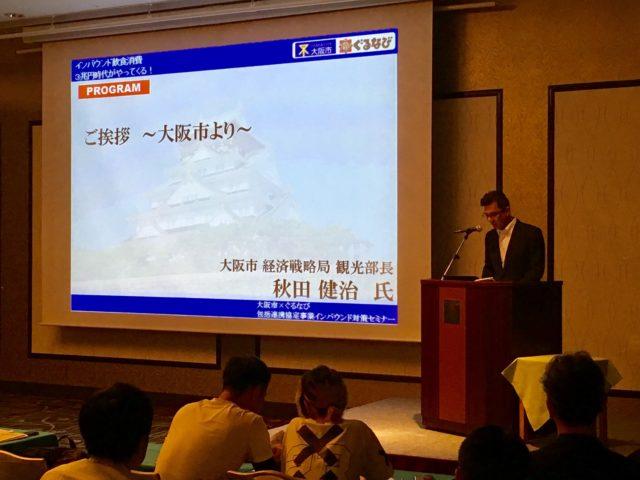 大阪市 観光部長の秋田さんが壇上で話しているところ