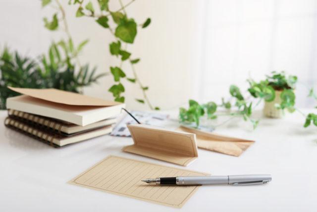 白いテーブルにレターセットとペンが置かれている画像