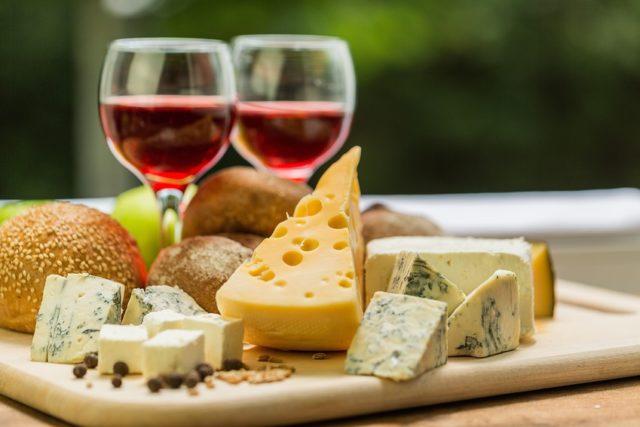 テーブルの上に赤ワインとチーズの盛り合わせが置かれている画像