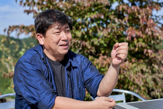 笑顔でベンチに座り右手を挙げている堀内氏の写真