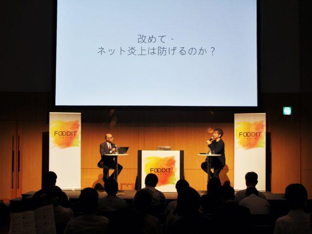 「改めて、ネット炎上は防げるのか?」と書かれたスライドの前で話す2人の写真