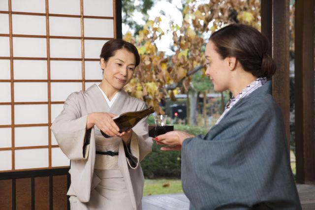 女将さんが浴衣姿の外国人女性にお酌している画像