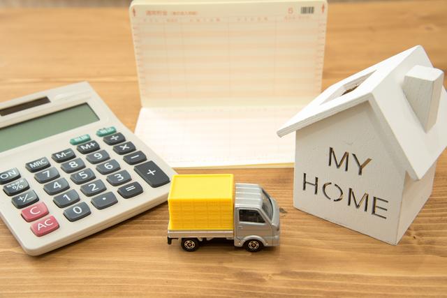 机の上に電卓、家の置物、トラックのミニカー