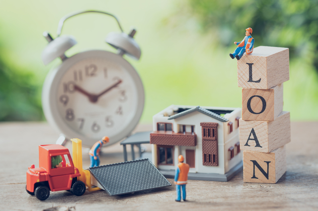 家の模型と赤いトラック。木片にLOANの文字