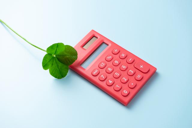 赤い電卓と四つ葉のクローバー