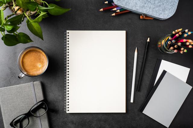 真ん中に真っ白のノートがあり、まわりに色鉛筆やコーヒーがある