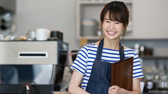 青白のボーダーTシャツを着た笑顔の女性カフェスタッフ