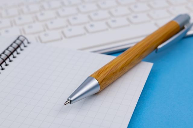 白のキーボードの手前にメモ帳とボールペン