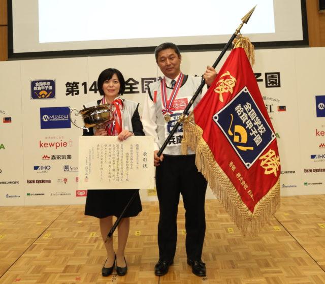 優勝した兵庫県丹波篠山市立西部学校給食センターの栄養教諭・田端 廣美さんと調理員・出野 年紀さんが優勝旗を持っている写真