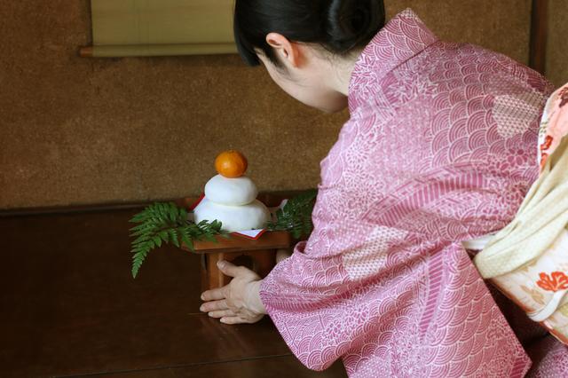 床の間に着物の女性が鏡餅を飾る画像